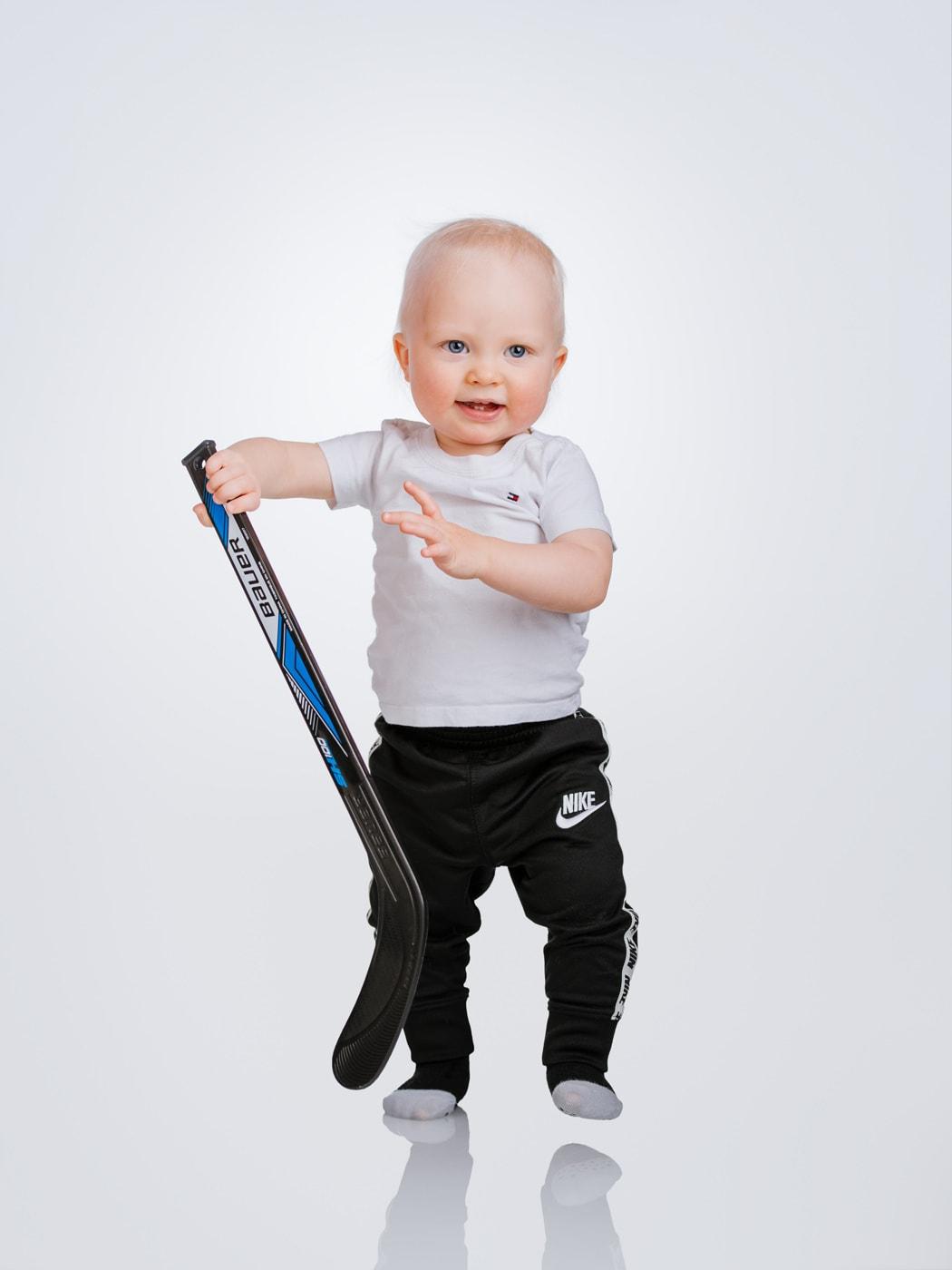 1-vuotiskuva jääkiekkomailan kanssa